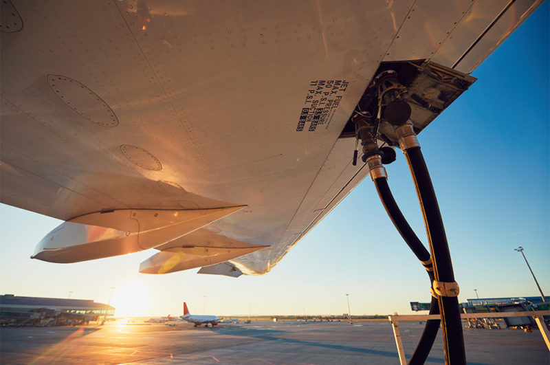 airplane refueling on airport runway with sunset