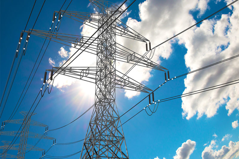 electric power lines and tower with blue sky and clouds